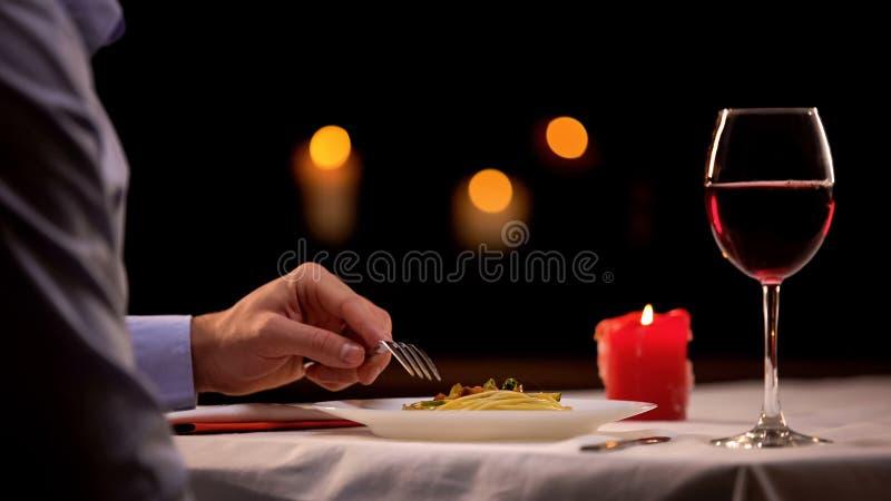 Αρσενικό που απολαμβάνει το γαστρονομικό γεύμα στο εστιατόριο, που τρώει τα ζυμαρικά και που πίνει το κρασί στοκ εικόνα