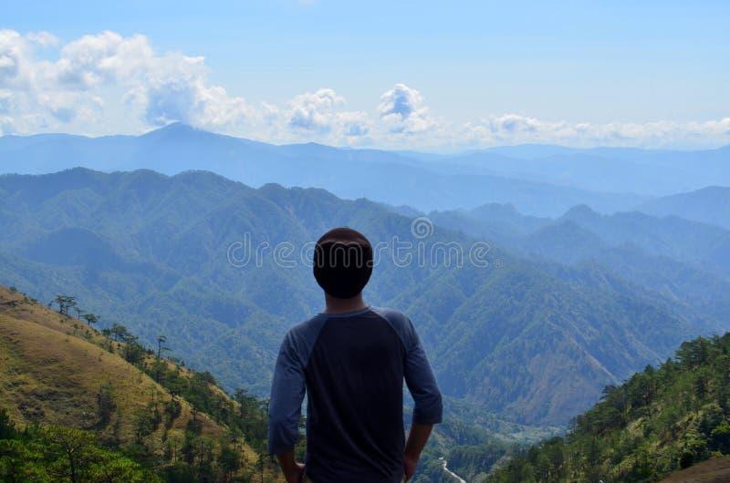 Αρσενικό που στέκεται σε έναν υψηλό απότομο βράχο και που εξετάζει το όμορφο τοπίο της ΑΜ Ulap, επαρχία Benguet στοκ φωτογραφία με δικαίωμα ελεύθερης χρήσης