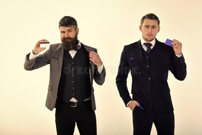 Αρσενικό πρόσωπο Ζητήματα που έχουν επιπτώσεις στο αγόρι Επιχειρηματίες, συνέταιροι στα κοστούμια που κρατούν τις πλαστικές πιστω στοκ φωτογραφία με δικαίωμα ελεύθερης χρήσης