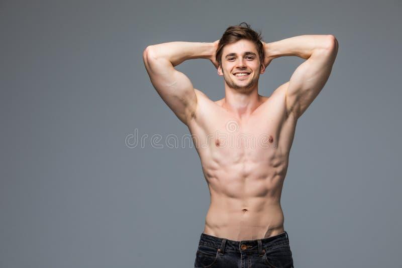 Αρσενικό πρότυπο ικανότητας με τον προκλητικό μυϊκό όμορφο καυτό νεαρό άνδρα πορτρέτου σωμάτων με το κατάλληλο αθλητικό σώμα στοκ εικόνα