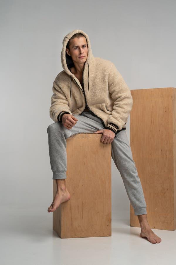 Αρσενικό πρότυπο sportwear στον ξύλινο κύβο που κοιτάζει μακριά στοκ εικόνες