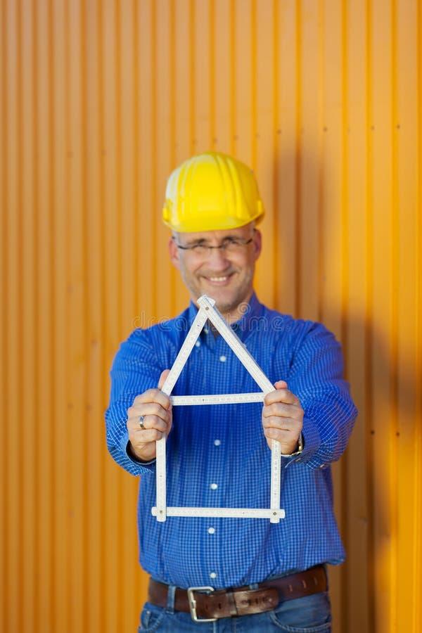 Αρσενικό πλαίσιο σπιτιών εκμετάλλευσης αρχιτεκτόνων ενάντια στο ρυμουλκό στοκ εικόνες με δικαίωμα ελεύθερης χρήσης