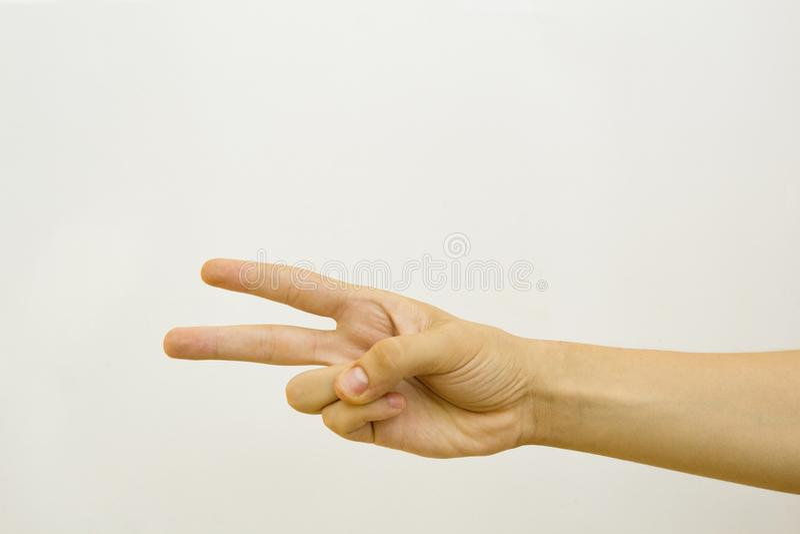 Αρσενικό χέρι με δύο δάχτυλα επάνω στο σύμβολο ειρήνης ή νίκης η ανασκόπηση απομόνωσε το λευκό στοκ φωτογραφίες