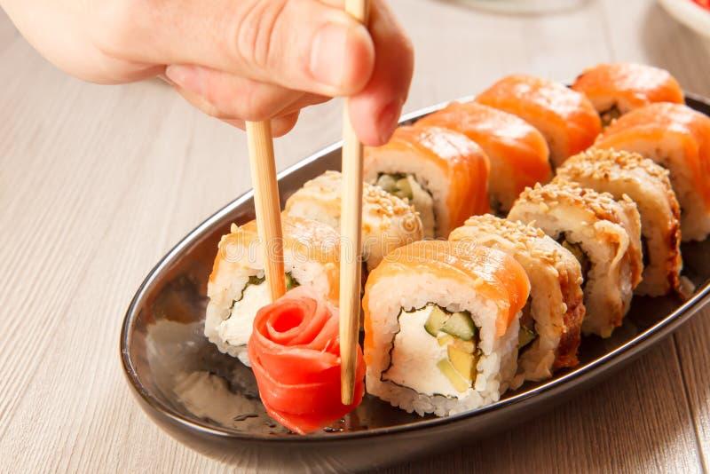 Αρσενικό χέρι με δύο chopsticks που κρατούν την παστωμένη πιπερόριζα στη μορφή στοκ φωτογραφία
