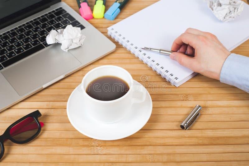 Αρσενικό χέρι με τη μάνδρα στο σημειωματάριο, το φλυτζάνι καφέ, τη μάνδ στοκ εικόνα με δικαίωμα ελεύθερης χρήσης