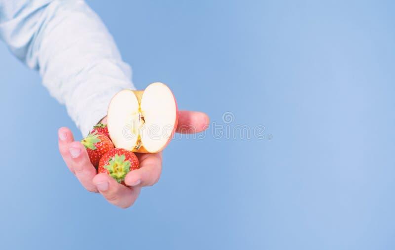 Αρσενικό χέρι με τις φράουλες και το μισό από το μπλε υπόβαθρο μήλων Οδηγίες οι ίδιοι Το χέρι προτείνει παίρνει τη φράουλα και το στοκ εικόνες