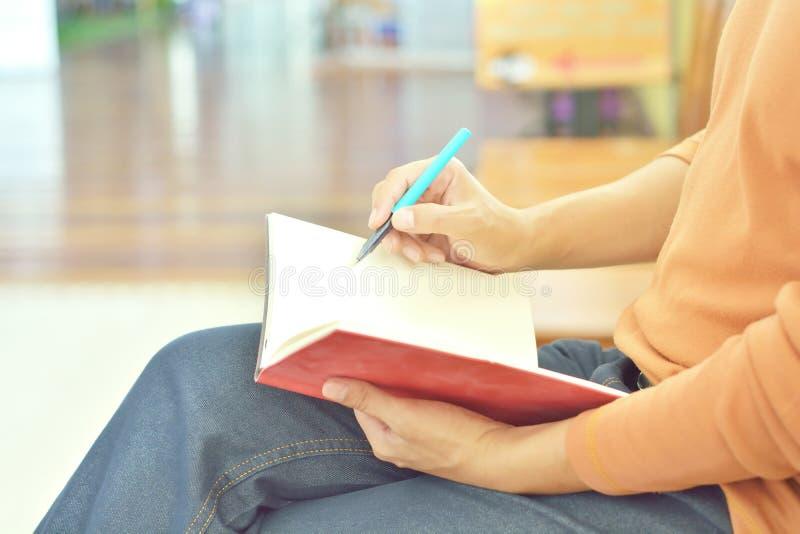Αρσενικό χέρι που γράφει ή που επισύρει την προσοχή στο σημειωματάριο ως μελέτη της έννοιας στοκ εικόνα