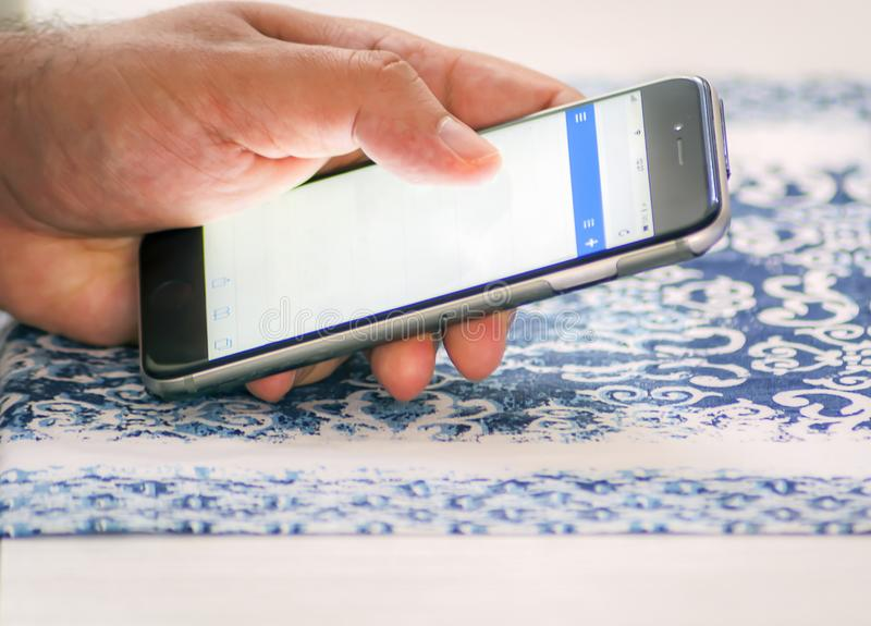 Αρσενικό χέρι που ελέγχει το ταχυδρομείο που χρησιμοποιεί ένα smartphone στοκ φωτογραφία