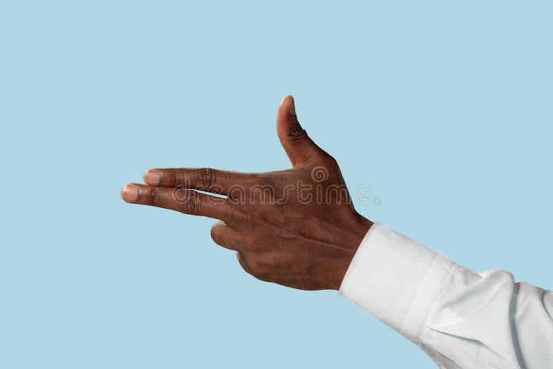 Αρσενικό χέρι που καταδεικνύει μια χειρονομία του πυροβόλου όπλου που απομονώνεται στο μπλε υπόβαθρο στοκ φωτογραφία με δικαίωμα ελεύθερης χρήσης