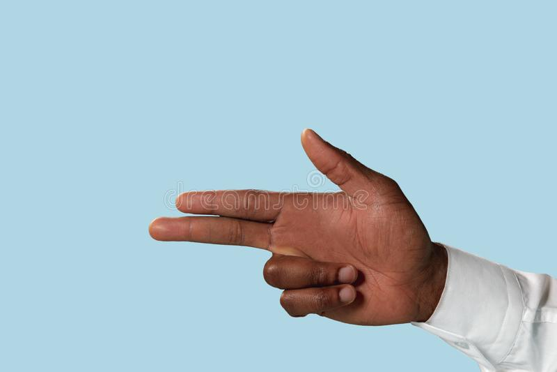 Αρσενικό χέρι που καταδεικνύει μια χειρονομία του πυροβόλου όπλου που απομονώνεται στο μπλε υπόβαθρο στοκ φωτογραφίες