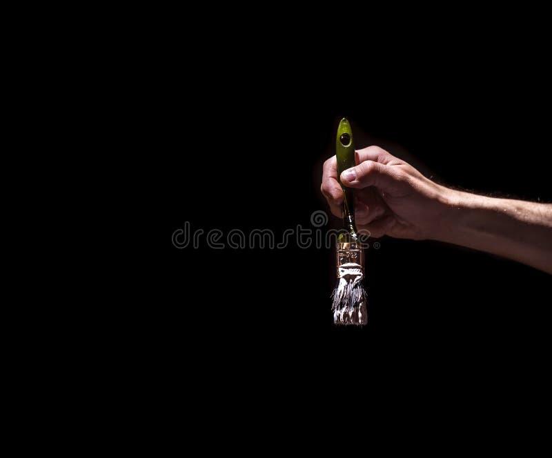 Αρσενικό χέρι που κρατά μια βούρτσα με το άσπρο χρώμα σε ένα μαύρο υπόβαθρο στοκ φωτογραφία με δικαίωμα ελεύθερης χρήσης