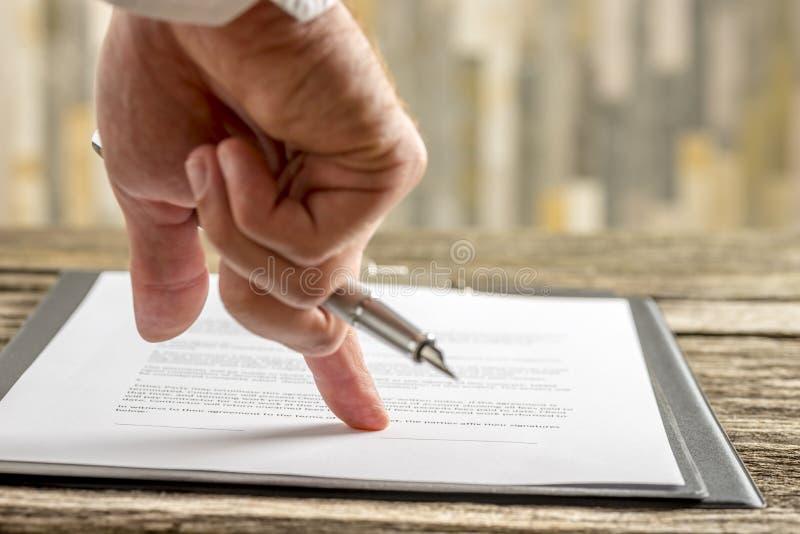 Αρσενικό χέρι που κρατά μια μάνδρα δείχνοντας μια γραμμή στο τέλος ενός contr στοκ φωτογραφία με δικαίωμα ελεύθερης χρήσης