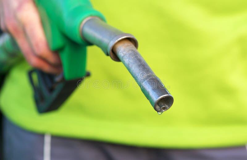 Αρσενικό χέρι που κρατά την πράσινη αντλία στο βενζινάδικο στοκ φωτογραφία με δικαίωμα ελεύθερης χρήσης