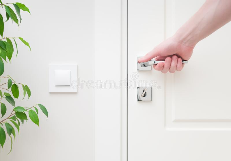 Αρσενικό χέρι που κρατά τη σύγχρονη λαβή πορτών Τα στοιχεία κινηματογραφήσεων σε πρώτο πλάνο του εσωτερικού στοκ εικόνες