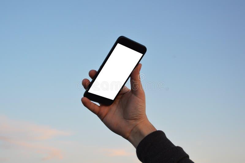 Αρσενικό χέρι που κρατά το έξυπνο τηλέφωνο στο υπόβαθρο ουρανού με το ψαλίδισμα της πορείας στοκ εικόνα