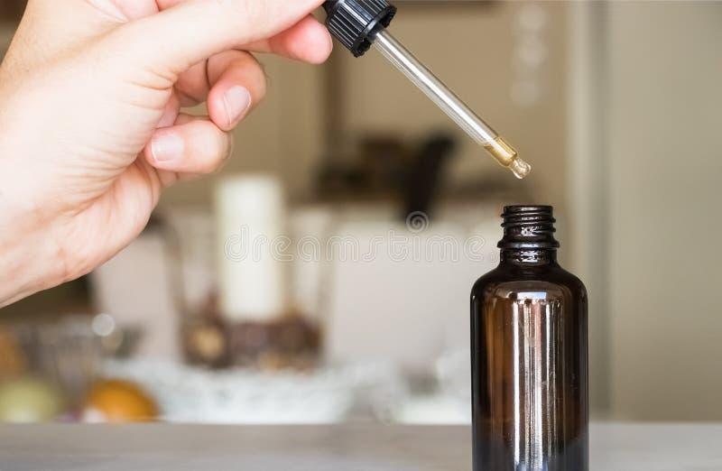 Αρσενικό χέρι που κρατά dropper με ένα μπουκάλι στοκ φωτογραφία με δικαίωμα ελεύθερης χρήσης