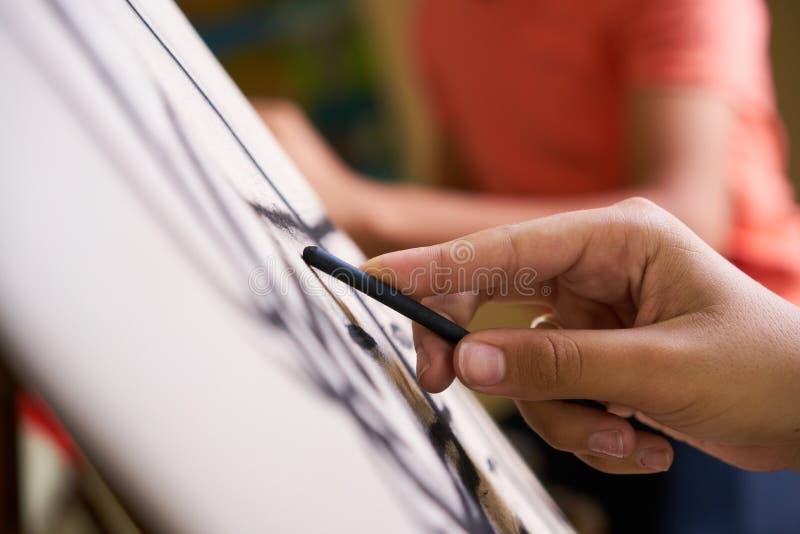Αρσενικό χέρι που σύρει το νεαρό άνδρα που σκιαγραφεί την κατάρτιση καλλιτεχνών στο σχολείο στοκ φωτογραφία με δικαίωμα ελεύθερης χρήσης