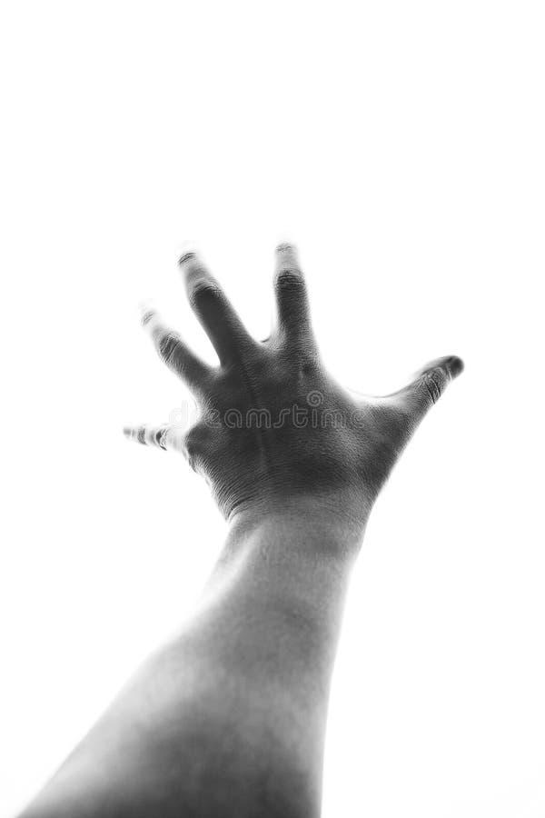 Αρσενικό χέρι που φθάνει έξω στο φως στοκ εικόνες