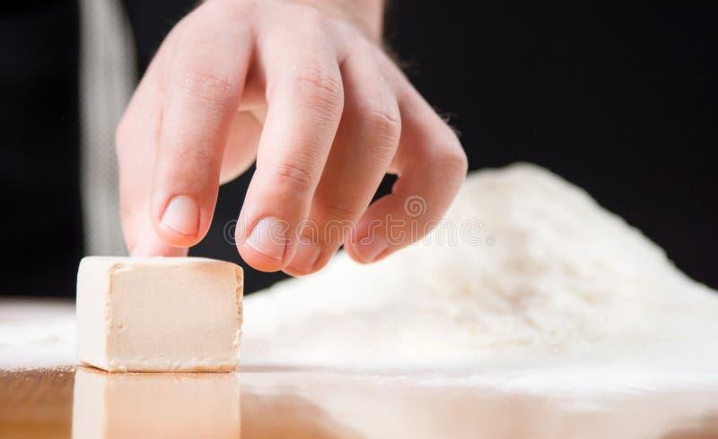 Αρσενικό χέρι που φθάνει στον κύβο ζύμης στον πίνακα ψησίματος στοκ φωτογραφία με δικαίωμα ελεύθερης χρήσης