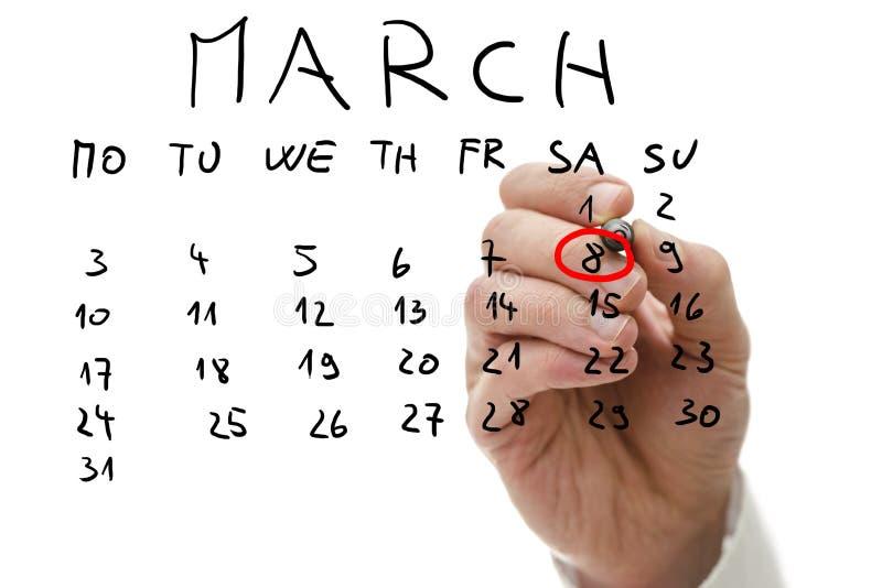 Αρσενικό χέρι που χαρακτηρίζει στο ημερολόγιο την ημερομηνία της 8ης Μαρτίου στοκ εικόνες με δικαίωμα ελεύθερης χρήσης