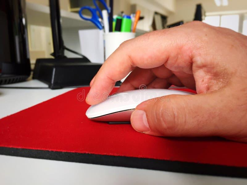 Αρσενικό χέρι που χρησιμοποιεί ένα άσπρο ποντίκι υπολογιστών στοκ εικόνες