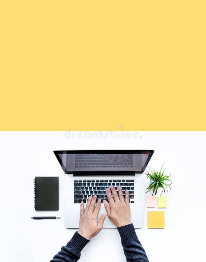 Αρσενικό χρησιμοποιώντας lap-top υπολογιστών στο άσπρο επιτραπέζιο υπόβαθρο γραφείων στοκ εικόνες