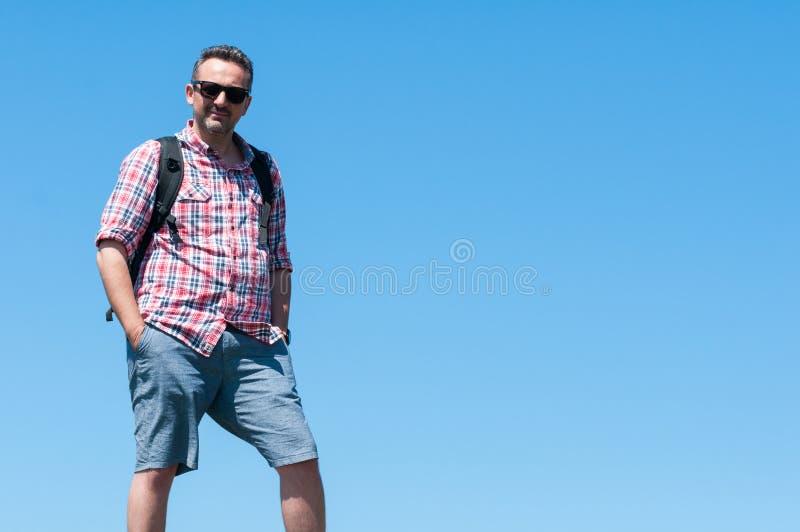 Αρσενικό backpacker που στέκεται με το υπόβαθρο μπλε ουρανού στοκ φωτογραφίες με δικαίωμα ελεύθερης χρήσης