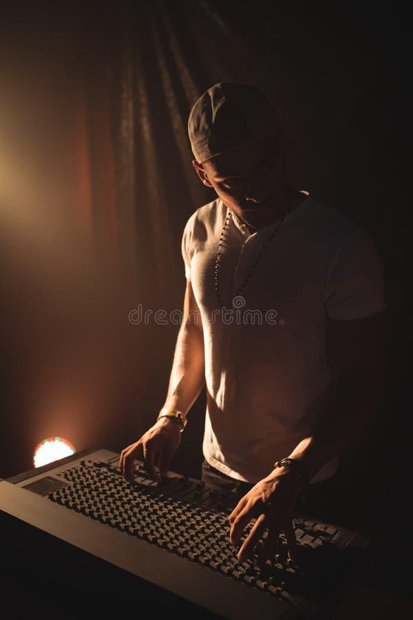 Αρσενικό DJ που ενεργοποιεί τον υγιή αναμίκτη στη συναυλία μουσικής στοκ εικόνες με δικαίωμα ελεύθερης χρήσης