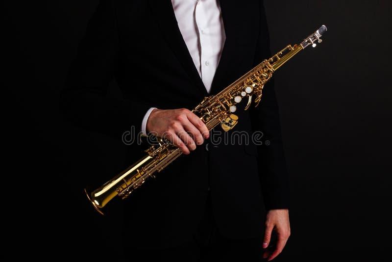 Αρσενικό saxophonist στο μαύρο κλασικό κοστούμι που κρατά ένα saxophone σοπράνο στεμένος σε μια μαύρη κινηματογράφηση σε πρώτο πλ στοκ φωτογραφίες