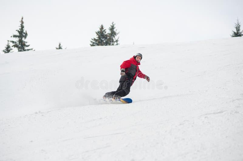 Αρσενικό snowboarder που οδηγά κάτω από το βουνό στη χειμερινή ημέρα στοκ φωτογραφία με δικαίωμα ελεύθερης χρήσης