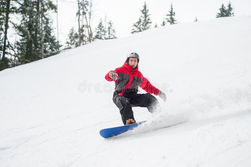 Αρσενικό snowboarder που οδηγά κάτω από το βουνό στη χειμερινή ημέρα στοκ φωτογραφία