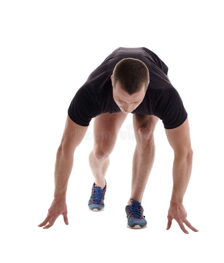 Αρσενικό sprinter που θέτει στον αρχικό φραγμό στοκ εικόνες