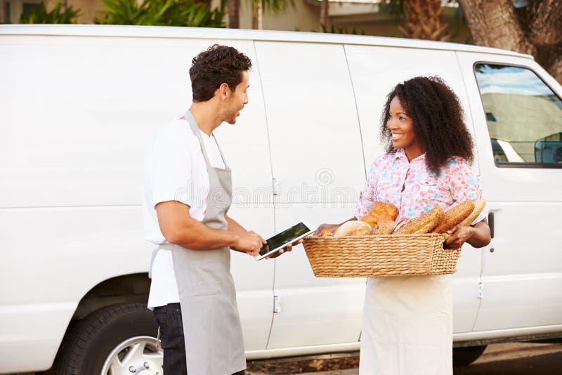 Αρτοποιοί που χρησιμοποιούν το ψηφιακό ψωμί εκφόρτωσης ταμπλετών από το φορτηγό στοκ εικόνα με δικαίωμα ελεύθερης χρήσης