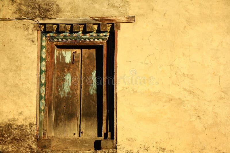 Αρχαία ξύλινη πόρτα στο ύφος του Νεπάλ με τον κίτρινο τοίχο στοκ εικόνα