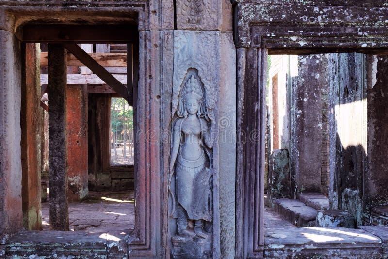 Αρχαία bas-ανακούφιση πετρών στον τοίχο ενός εγκαταλειμμένου Khmer ναού Πέτρινο γλυπτό μιας γυναίκας στοκ φωτογραφία με δικαίωμα ελεύθερης χρήσης