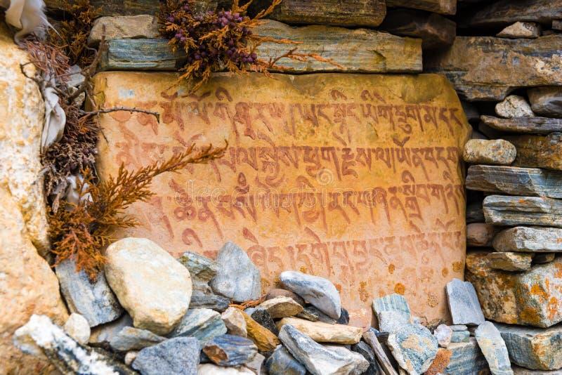 Αρχαίες βουδιστικές χαρασμένες πέτρες με τα ιερά θρησκευτικά mantras στην πορεία οδοιπορίας στην περιοχή συντήρησης Annapurna, Νε στοκ φωτογραφία