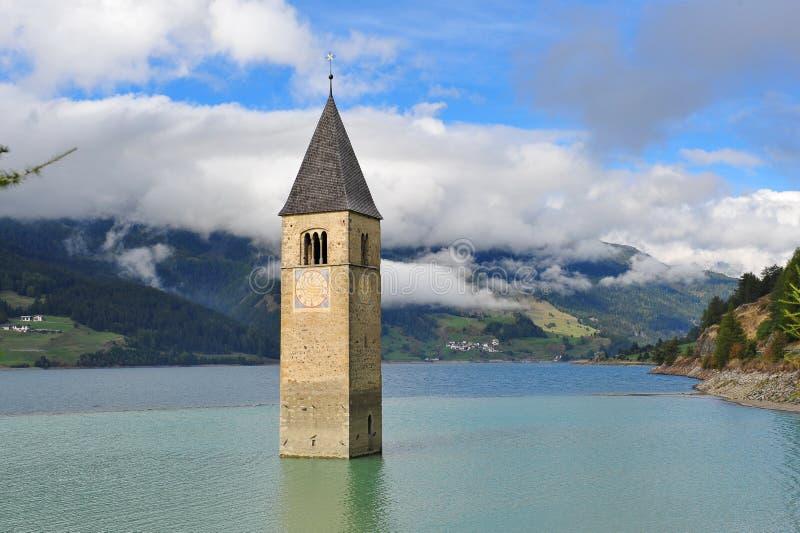 Αρχαίος μισό-καταδυμένος πύργος κουδουνιών σε Graun im Vinschgau στοκ φωτογραφία με δικαίωμα ελεύθερης χρήσης