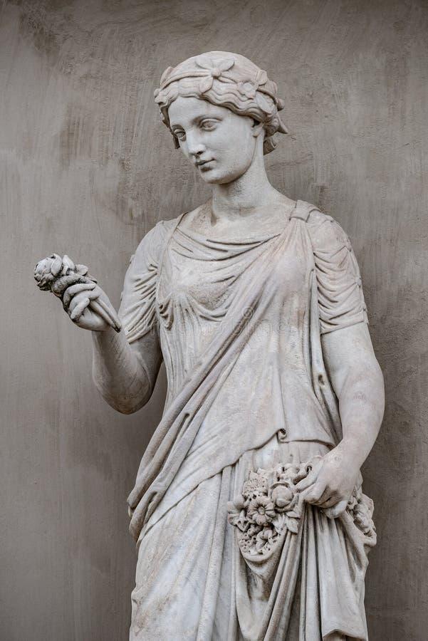 Αρχαίο άγαλμα της αισθησιακής ελληνικής γυναίκας εποχής αναγέννησης με ένα flo στοκ φωτογραφία