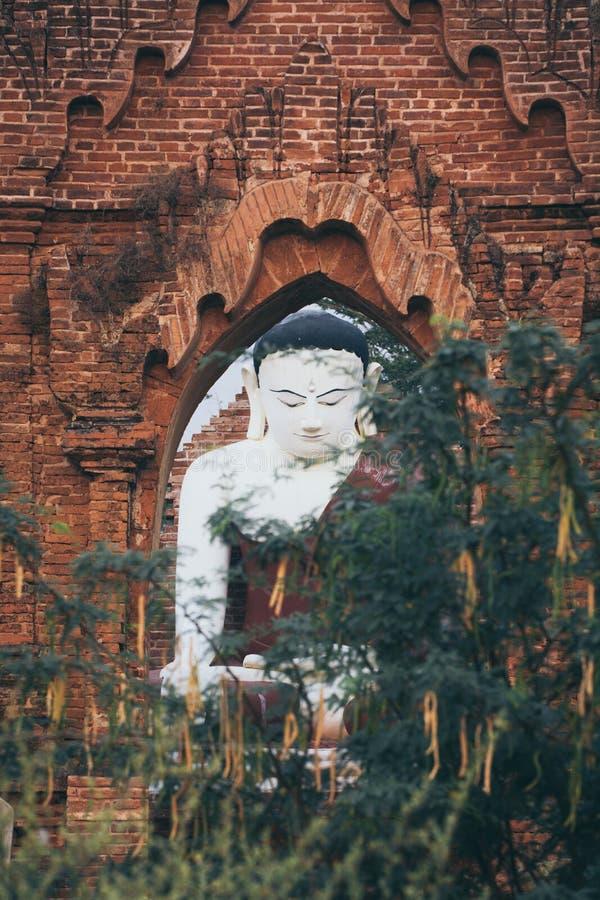 Αρχαίο άγαλμα του Βούδα που πλαισιώνεται με την αψίδα τούβλου στο ναό Bagan, το Μιανμάρ στοκ φωτογραφίες με δικαίωμα ελεύθερης χρήσης