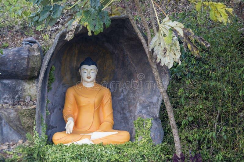 Αρχαίο βουδιστικό γλυπτό του Βούδα στα πορτοκαλιά ενδύματα στοκ εικόνα με δικαίωμα ελεύθερης χρήσης