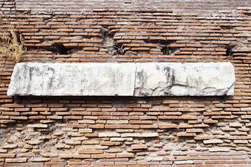 Αρχαιολογικές ανασκαφές σε Ostia Antica: Ρωμαϊκός τοίχος με το μάρμαρο που χαράσσεται με τις λατινικές επιστολές στοκ εικόνες