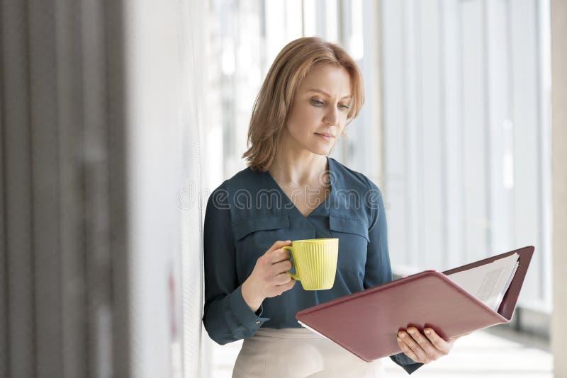 Αρχείο ανάγνωσης επιχειρηματιών που έχει τον καφέ στο γραφείο στοκ φωτογραφίες με δικαίωμα ελεύθερης χρήσης