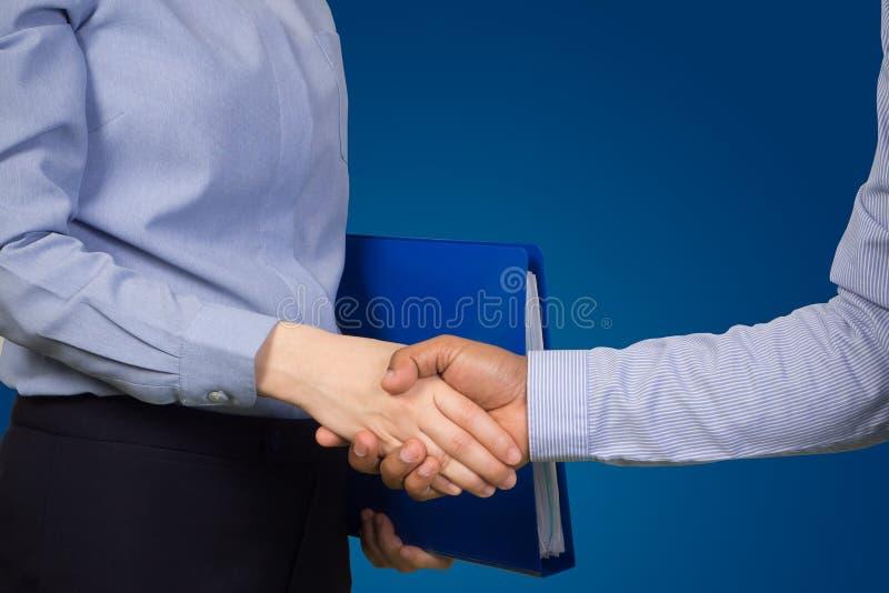 Αρχείο και χειραψία εγγράφων εκμετάλλευσης επιχειρηματιών με τον πελάτη στο απομονωμένο μπλε υπόβαθρο στοκ εικόνες με δικαίωμα ελεύθερης χρήσης