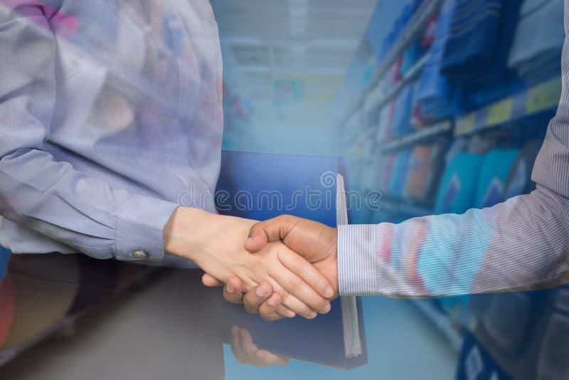 Αρχείο και χειραψία εγγράφων εκμετάλλευσης επιχειρηματιών με τον πελάτη στοκ φωτογραφίες