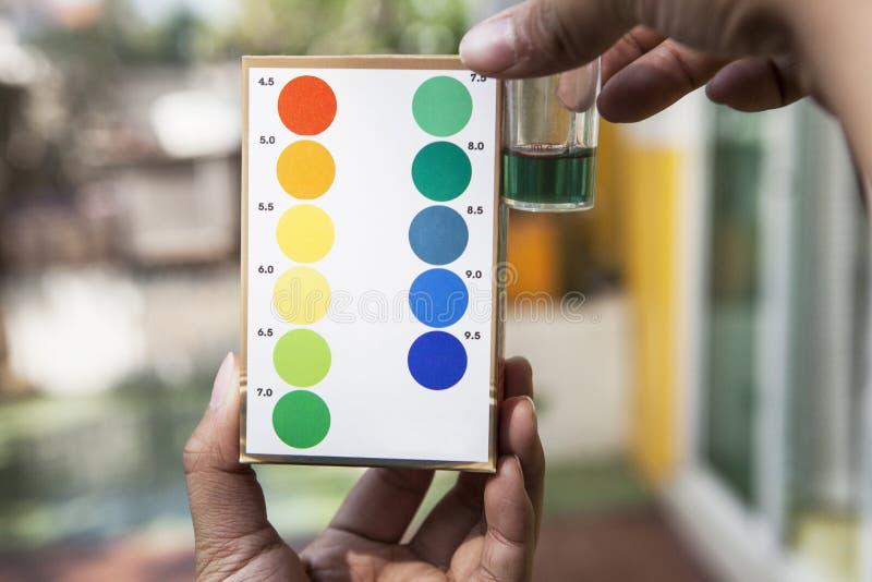 Αρχείο της εξεταστικής δοκιμής νερού pH εκμετάλλευσης χεριών που συγκρίνει το χρώμα με μέσα στοκ εικόνες