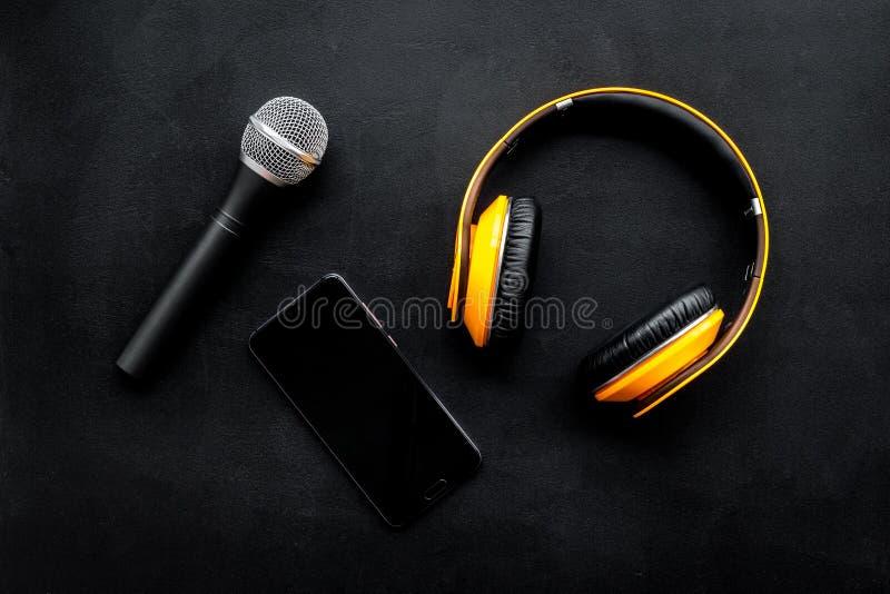 Αρχείο Podcast με το τηλέφωνο, το μικρόφωνο και τα ακουστικά στο μαύρο διάστημα άποψης υποβάθρου τοπ για το κείμενο στοκ εικόνες