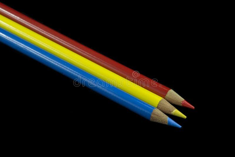 3 αρχικά χρωματισμένα μολύβια στοκ εικόνες
