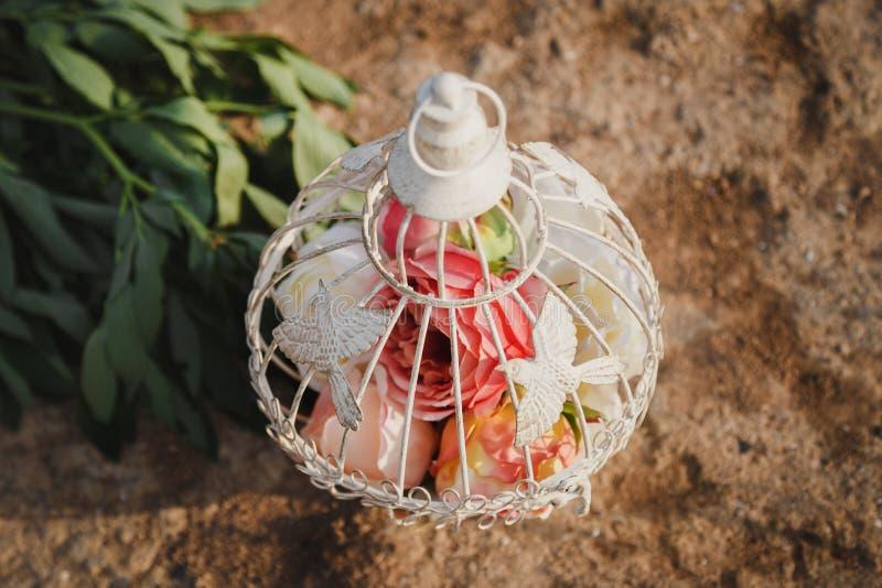 Αρχική γαμήλια floral διακόσμηση με μορφή κλουβιού με τα λουλούδια μέσα στη στάση στην άμμο, υπαίθρια γαμήλια τελετή παραλιών στοκ φωτογραφία με δικαίωμα ελεύθερης χρήσης