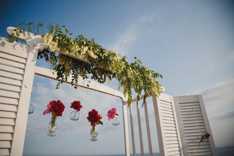 Αρχική γαμήλια floral διακόσμηση στη μορφή μίνι βάζων και τις ανθοδέσμες των λουλουδιών που κρεμούν από το γαμήλιο βωμό, υπαίθριε στοκ εικόνα με δικαίωμα ελεύθερης χρήσης