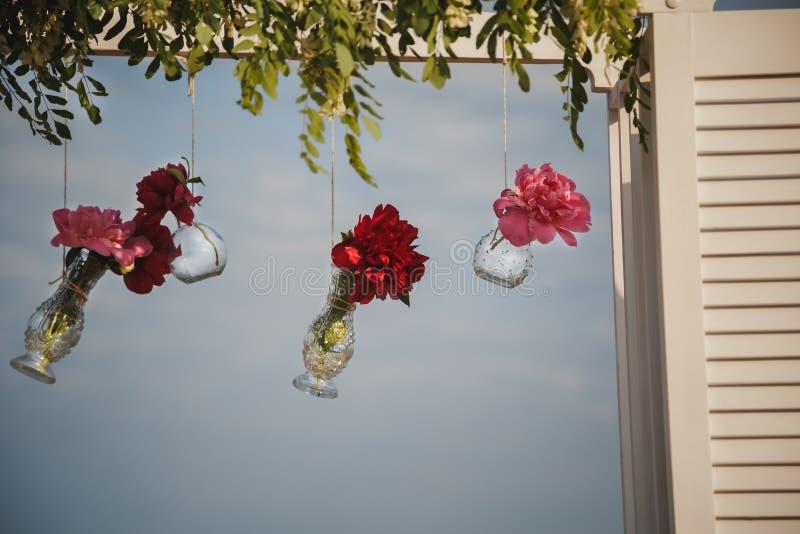 Αρχική γαμήλια floral διακόσμηση στη μορφή μίνι βάζων και τις ανθοδέσμες των λουλουδιών που κρεμούν από το γαμήλιο βωμό, υπαίθριο στοκ φωτογραφίες με δικαίωμα ελεύθερης χρήσης